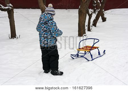 Walking outdoors in the winter. The child sits on his haunches in the snow and plays with colorful sleds.