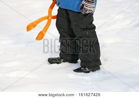 Children's winter games outdoors. The image of the child who is using a plastic toy makes balls-snowballs from snow.