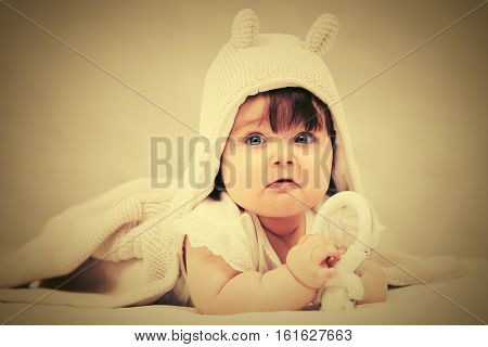 Baby girl with a toy crawling on blanket indoors