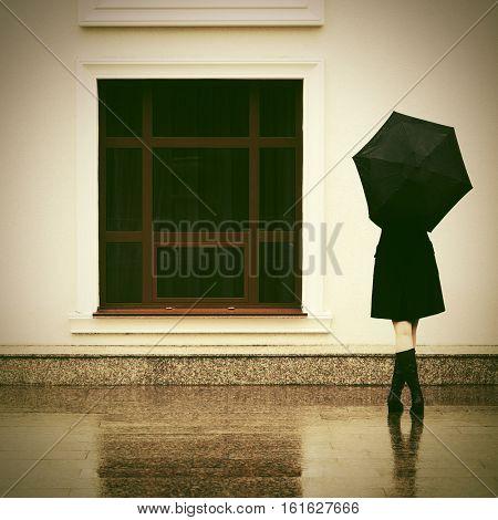 Woman with umbrella in the rain. Stylish fashion model outdoor