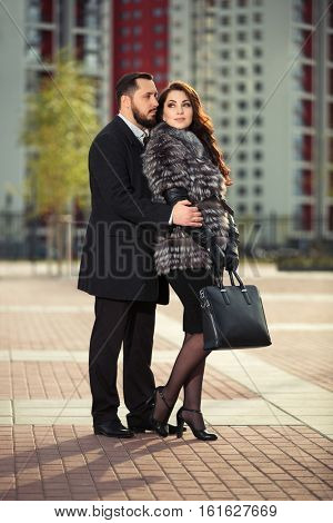 Happy young couple in love walking on city street. Stylish fashion model outdoor