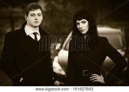 Young business couple next to car parking. Stylish fashion model in black coat outdoor