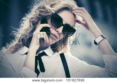 Young business woman in sunglasses calling on mobile phone. Stylish fashion model with long curly hairs outdoor