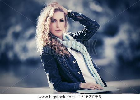 Young woman in denim jacket walking on city street. Stylish fashion model with long curly hairs outdoor