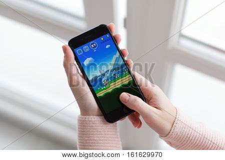 Alushta Russia - November 19 2016: Woman hand holding iPhone 7 Jet Black with game Super Mario Run in the screen. Games Super Mario Run was created and developed by the Nintendo.