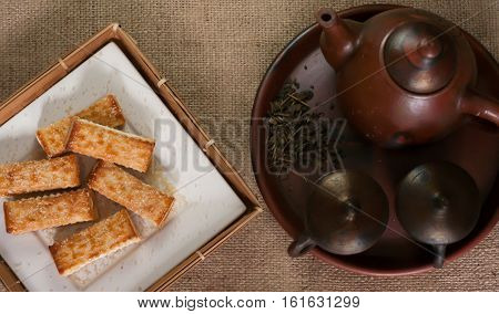 pastries and hot tea in a teapot traditional Indonesian, design a calm and relax