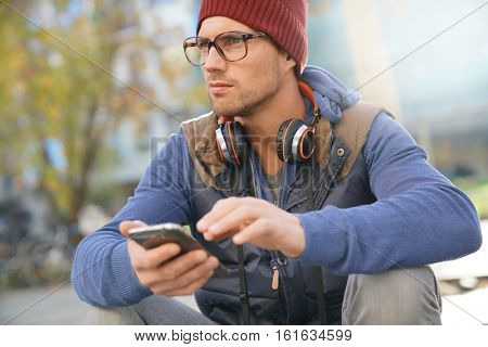 Hipster guy in town using smartphone