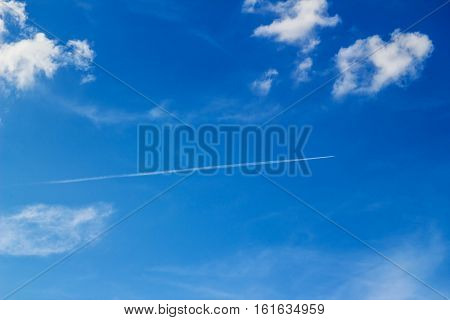 Plane leaving white lines against the blue sky and clouds.