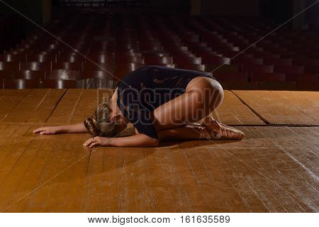 Professional ballet dancer lying on the stage after the performance. Art concept.