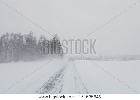 Car driving on a snowy road in a snow storm with no visibility