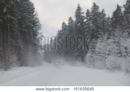 Red car driving on a snowy road in the woods in a snow storm