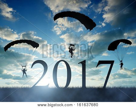 Silhouette skydiver parachutist landing in to the New Year 2017 at sunset