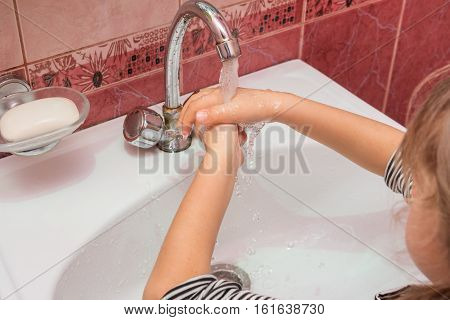 Five year girl washes hands with soap