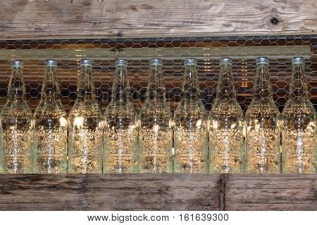 Yellow Drink Bottles with silvery cap on Wooden Shelf behind Metallic Net Alcoholic Aperitif