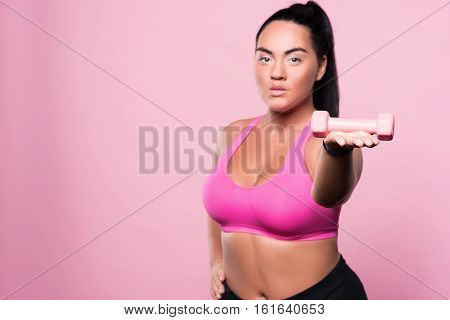 One of methods. Pretty young mulatto lady standing against isolated pink background with small dumbbell on her palm.