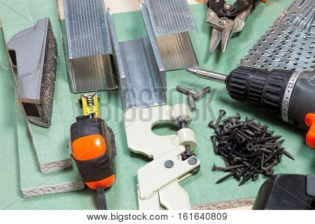 Plasterboard tools set with metal studs, screws, tape measure, screwgun and punch lock crimper