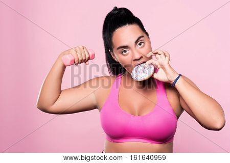 Cheating on yourself. Funny plump mulatto woman doing dumbbell exercises and eating donut against pink isolated background.