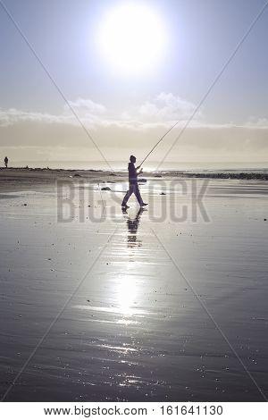 lone fisherman fishing on the beach in Ballybunion county Kerry Ireland