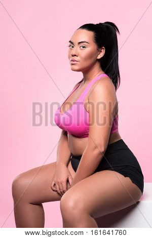 Inner beauty. Portrait of pretty chubby mulatto lady sitting and looking forward against isolated pink background.