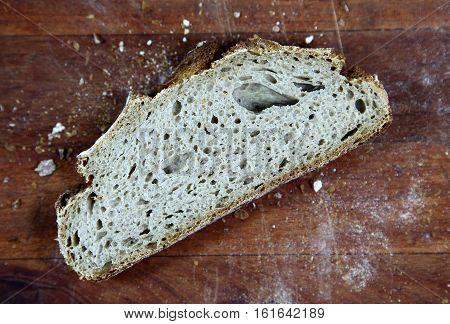 Loaf of sliced whole grain bread on wood bread board