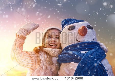 Happy child girl playing with a snowman on snowy winter walk in nature. Frost winter season.