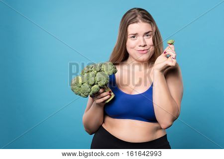 So cute. Attractive funny overweight girl holding broccoliand in one hand and small ripped off peace isolated on blue background.