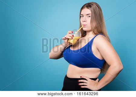 Enjoying healthy diet. Overweight woman drinking orange juice and holding arms on hips while standing isolated on blue background.