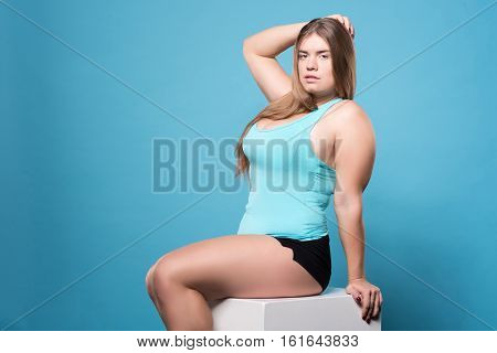 Being sexy. Attractive youthful chubby woman sexy posing while sitting against isolate blue background.