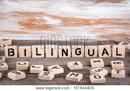 Bilingual from wooden letterson on wooden background.