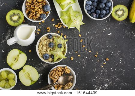 Ingredients for a healthy breakfast, avocado, quinoa bowl, carambola, green apple, banana, kiwi, nuts, oatmeal, berries fruits blueberry almonds walnuts Top view Greenery