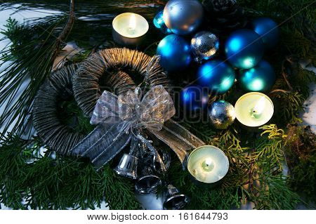 Christmas decorations and candles against the background of pine branches