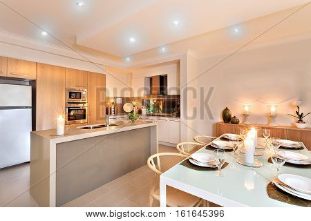 Modern kitchen with white fridge next to the wall oven surrounded by wooden pantry cupboards well prepared for serving with flashing candles on the counter and at the dinner table with white dishes and wine glasses around it.