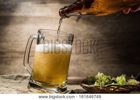 On empty wooden background beer flows from bottle in mug