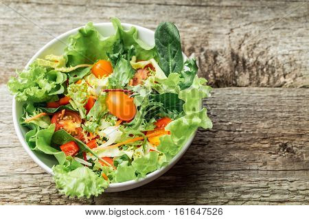 Salad with fresh vegetables - tomatoes, carrots, bell peppers and mixed greens - arugula, mesclun, mache - on wooden background.