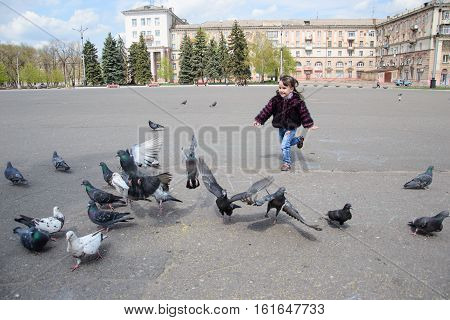 Child running after pigeons. Girl playing with pigeons doves birds in city park