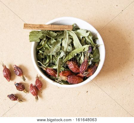 cup with dried grass wild rose and cinnamon set to brew green tea useful