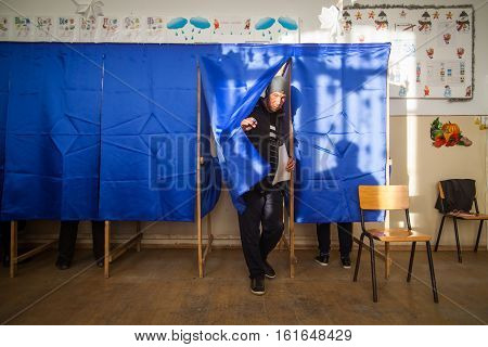 Bucharest Romania - December 11 2016: A man exits a voting booth during voting for parliamentary elections at a polling station in Bucharest Romania.