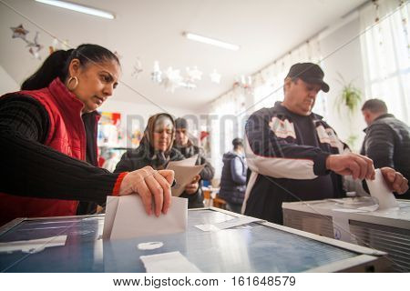 Bucharest Romania - December 11 2016: A woman casts her ballot during voting for parliamentary elections at a polling station in Bucharest Romania.