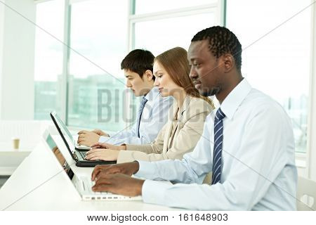 Three business people sitting at one table in a row and working with laptops
