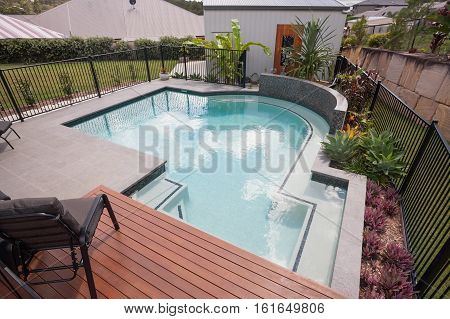 Outdoor patio area with a swimming pool including chairs and fence beside the garden and house