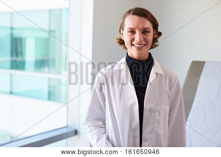 Portrait Of Female Doctor Wearing White Coat In Exam Room