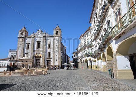 EVORA, PORTUGAL - OCTOBER 8, 2016: Giraldo Square with Santo Antao Church and typical house facades and arcades