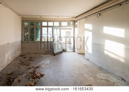 Old abandoned house. The room is destroyed the walls are broken trash on the floor chaos.