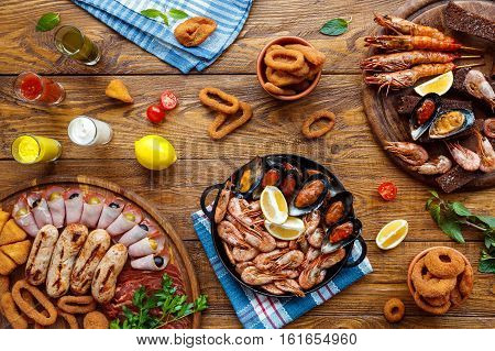 Seafood platter top view, flat lay. Mediterranean cuisine restaurant food, fried calamari rings, shrimps, mussels, oysters, shellfish delicacy on wood table background. Catering, banquet table poster