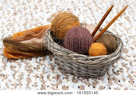 Colorful yarn in balls and wooden needles lies in braided basket near coil of yarn