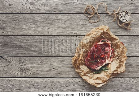 Raw beef steak in craft paper, food background. Top view with copy space on gray rustic wood. Fresh juicy meat, rosemary and herbs. Cooking ingredients, butcher's and grocery concept, filtered