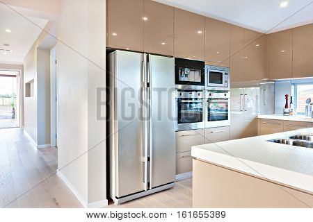 Expensive and modern kitchenware including silver color and tall two door refrigerator and four ovens and stoves fixed to the wall with cabinets around it. There is a ceramic countertop with sink very closely. The wooden floor covers the whole house