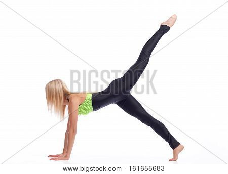 Sexy sports. Shot of a fitness woman with strong sexy body stretching at studio holding her leg up in the air doing plank exercise isolated copyspace body figure sexy sports fitness concept