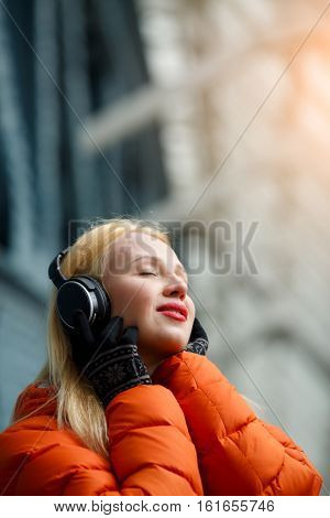 Ginger with earphones listening music in building
