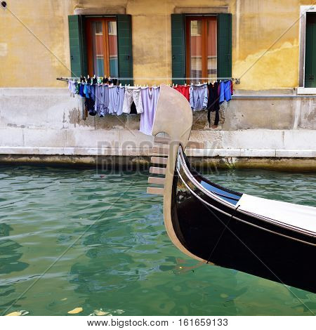 Prow of the gondola on the Venetian water canal with and handing linen on background colorful facade. Venice Italy